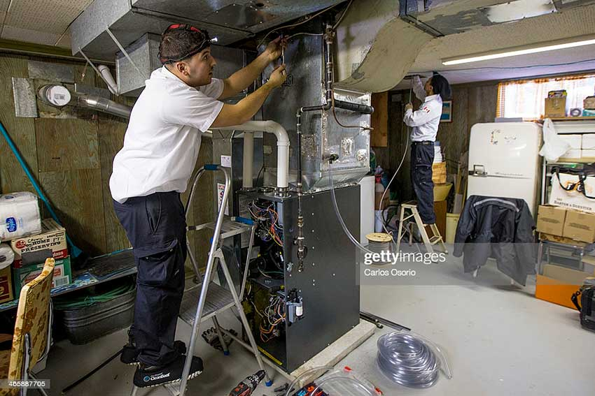 TORONTO, ON - JANUARY 29: Service technician from Air Quality Dunrite, Kyle Lopes, repairs a furnace on Wednesday January 29, 2014 in Toronto. There has been a spike in sales because of extreme cold weather this winter.        (Carlos Osorio/Toronto Star via Getty Images)